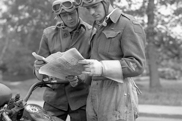 Despatch riders Doug Reid and Norman Given of the 9th Canadian Infantry Brigade checking the route of a convoy taking part in a training exercise, England on May 17, 1944. Credit: Lieut. H. Gordon Aikman / Canada. Dept. of National Defence / Library and Archives Canada / PA-159936