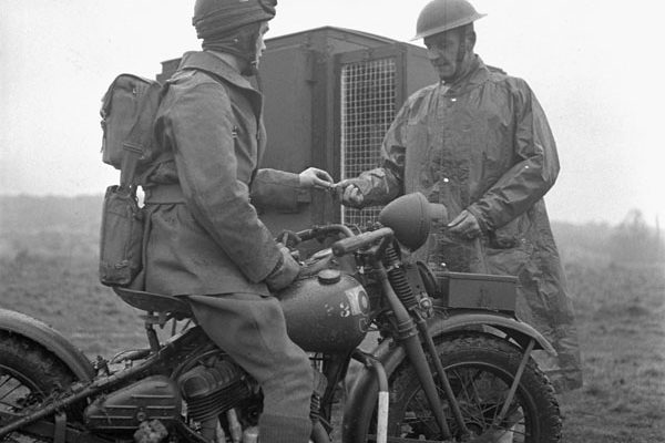 Despatch rider Private J.W. King (left), who is riding a Harley-Davidson motorcycle, accepts a pigeon message from Corporal J. Hanley, Royal Canadian Corps of Signals (R.C.C.S.), England on February 10, 1943. Photo credit: Lieut. Alexander M. Stirton / Canada. Dept. of National Defence / Library and Archives Canada / PA-166940