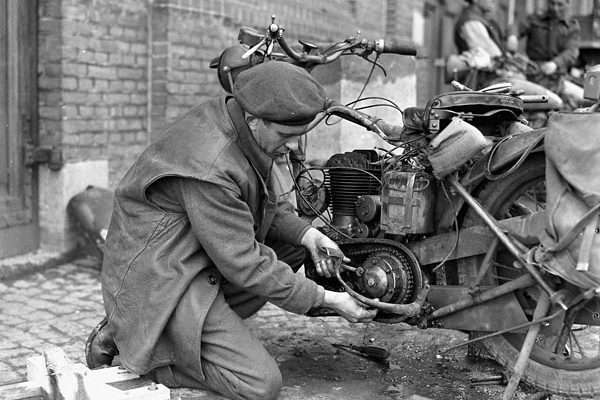 Craftsman C.S. Keith, 11th Infantry Brigade Workshop, Royal Canadian Electrical and Mechanical Engineers (R.C.E.M.E.), repairing a motorcycle, Groningen, Netherlands on April 28, 1945. Photo credit: Capt. Jack H. Smith / Canada. Dept. of National Defence / Library and Archives Canada / PA-191182