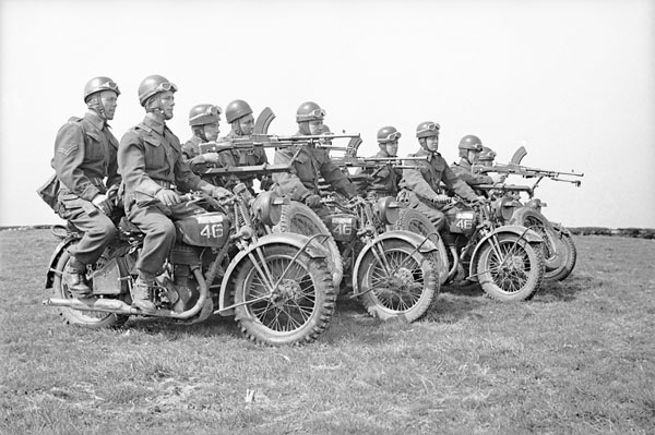 Four motorcycle Bren gun teams of the Royal Montreal Regiment taking part in a training exercise at Petworth Camp, England, on April 28, 1942. The motorcycles are Heavy WLC Harley Davidsons with sidecars which incorporate special Bren gun mounts. Photo credit: Lieut. C.E. Nye / Canada. Dept. of National Defence / Library and Archives Canada / PA-211309