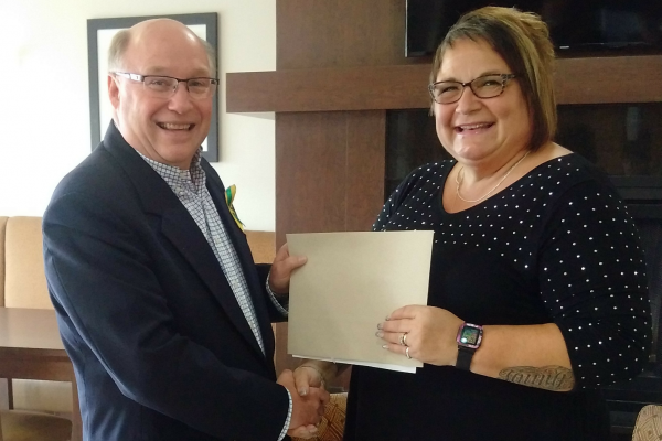 Dr. Robert Kitchen MP presenting 1st place winner Pam Currie with her Motorcyclist Making a Difference certificate.