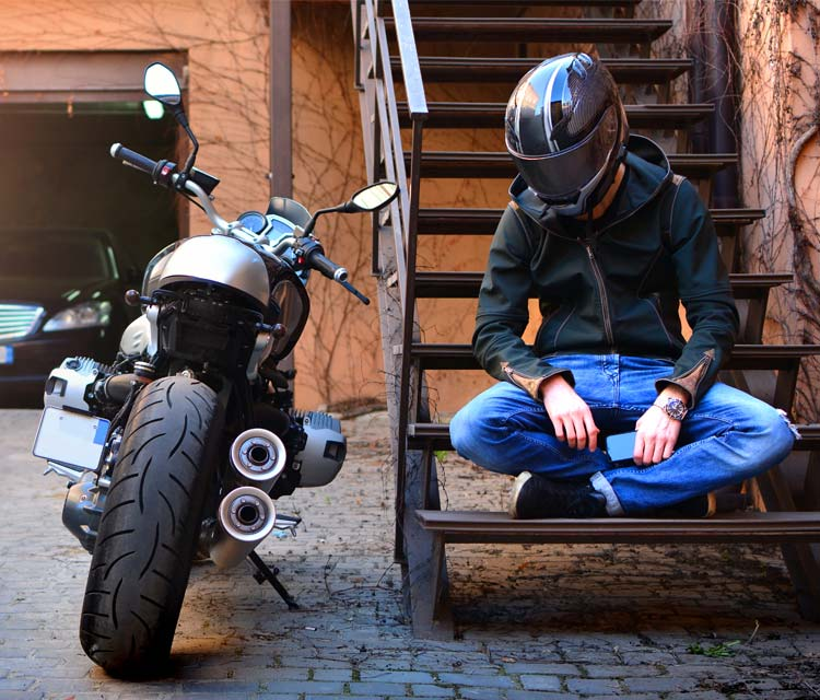 motorcycling during the pandemic - Motorcyclists Confederation of Canada - image of a motorcyclist wearing his helmet, sitting on stairs next to his bike, looking sad