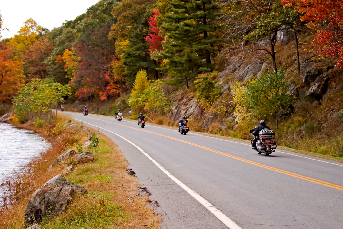 Motorcycling.ca Blog article - group of motorcyclists riding by a lake with beautiful fall colour
